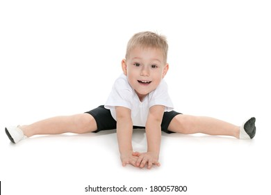 Little boy performs gymnastic exercises on the white background