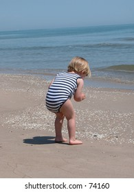 Little boy picking up a shell on the beach.