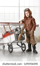 Little boy in a pilot's suit playing with an airplane in the room