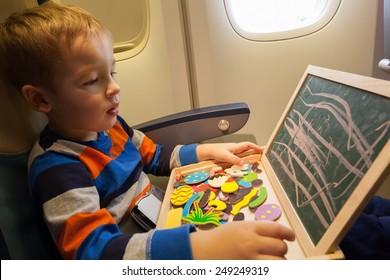 Kleiner Junge im Flugzeug, der mit Kreide auf ein kleines Brett zeichnet. Unterhaltung während des Fluges