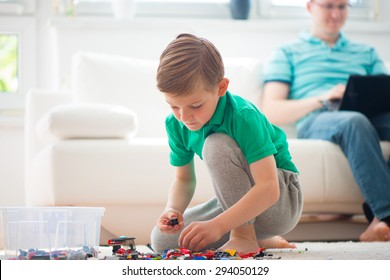 Little boy play with building kit, father works with laptop