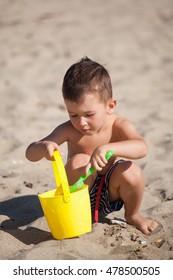 little boy play with sand on summer beach