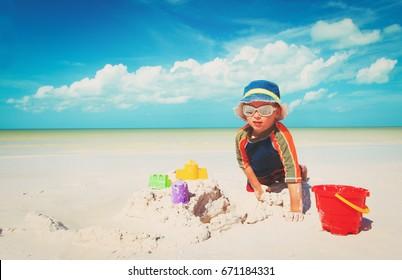 little boy play with sand on beach