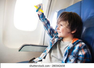 Little boy play with toy plane in the commercial jet airplane flying on vacation