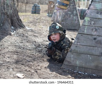 Little boy player with gun during laser tag game.
