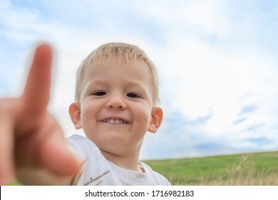 Little boy playfuly pointing to camera