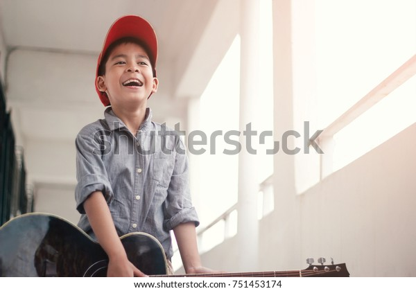 Little boy playing a acoustic guitar on the floor at home