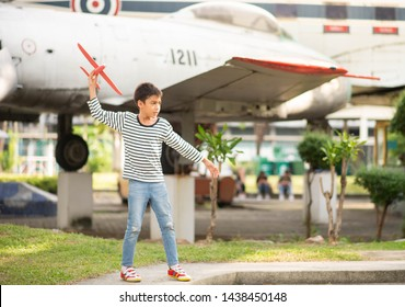Little boy playing airplane with plane background
