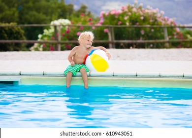 Little boy playing ball in outdoor swimming pool jumping into water on summer vacation on tropical beach island. Child learning to swim in pool of luxury resort. Water toy for kids