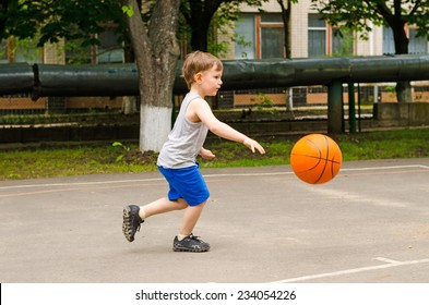 Little boy playing basketball running along the court in his sports wear bouncing the ball, side view outdoors