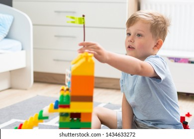 The little boy is playing with blocks in his room