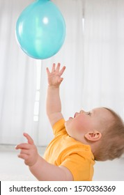 A little boy playing with a blue balloon