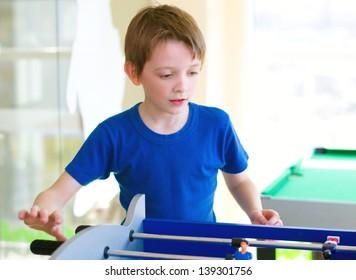 little boy playing board football