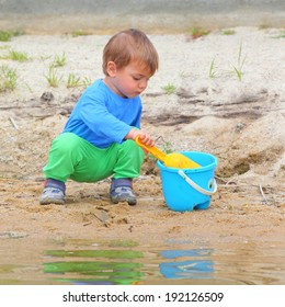 Little boy playing with bucket and spade on the beach.
