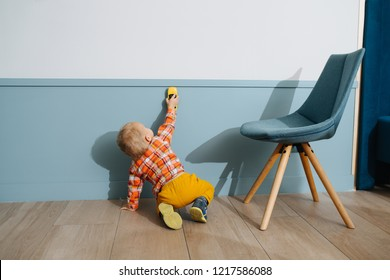 Little boy playing with car toy on white wall background