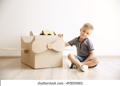 Little boy playing with cardboard airplane on white wall background