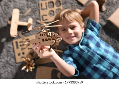 Little boy playing with cardboard helicopter on floor at home, top view. Creative hobby