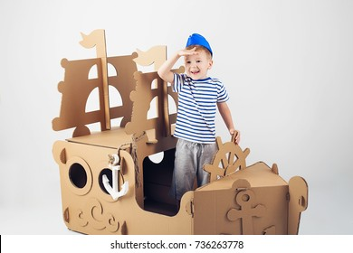 Little boy playing with cardboard ship on white background. Happy kids. Cute child dressed as a sailor. Childhood. Fantasy, imagination.