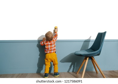 Little boy playing with cartoy on white wall background