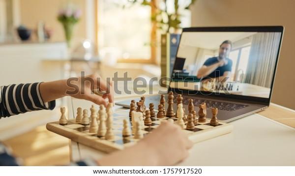 Pequeño niño jugando al ajedrez con su maestro de ajedrez, usa laptop para videollamadas. El Niño Aprende A Jugar Al Ajedrez A Través De Internet. Educación remota en línea, educación electrónica, aprendizaje a distancia. Más de hombro