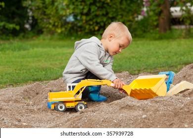 Little boy playing with children excavator in the sandbox.