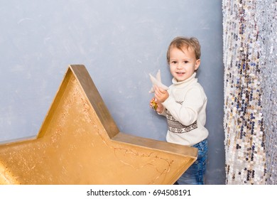 Little boy playing with Christmas stars