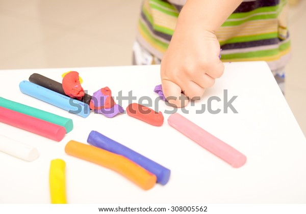 little boy playing with clay dough, education and daycare concept