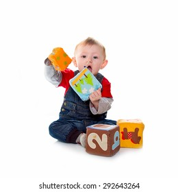 little boy playing with colored soft cube isolated on white
