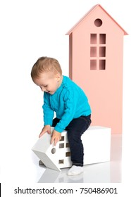 A little boy is playing with colorful houses. The concept of family happiness, the development of the child in kindergarten or in the family. Isolated on white background.