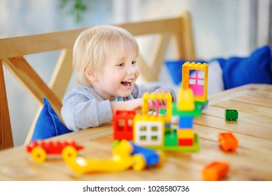 Little boy playing with colorful plastic blocks at kindergarten or at home. Development toys for preschooler children