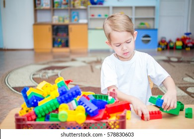 Little boy playing with colorful plastic blocks. Construction of various facilities . Educational games in kindergarten.
