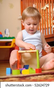 Little boy is playing with colorful toy blocks