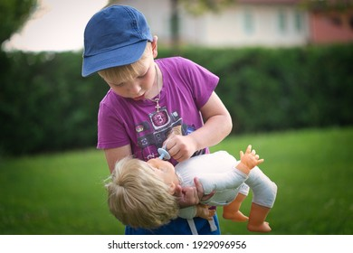 little boy playing with a doll in nature 2021