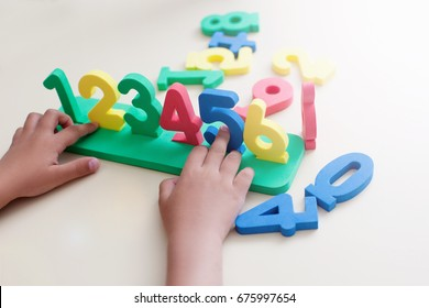 Little boy Playing with figures, early education, Mathematics and numeracy. Top view no face