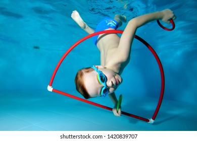 A little boy is playing fun, tumbling underwater at the bottom of the pool. Dancing underwater. Creative. Open his eyes. Portrait. Underwater photography. Horizontal orientation of the image
