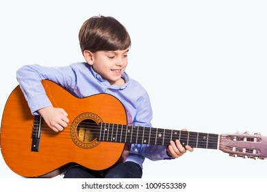 Little boy is playing the guitar at home isolated in white