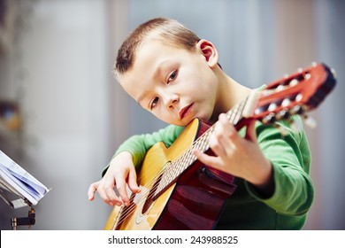Little boy is playing the guitar at home