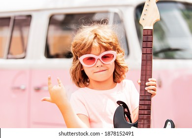 Little boy playing guitar like a rock-star. Rock and roll child. Funny kid on pink background