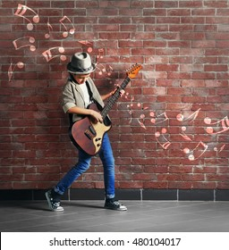 Little boy playing guitar. Musical notes design on brick wall background.