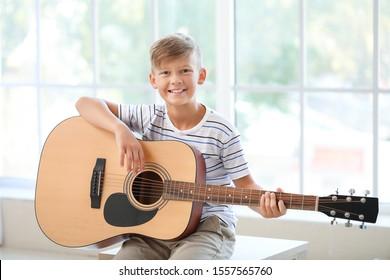 Little boy playing guitar near window
