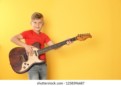 Little boy playing guitar on color background. Space for text
