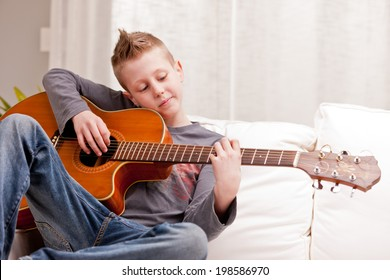 little boy playing guitar on a sofa in his living room