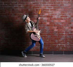 Little boy playing guitar on a brick wall background