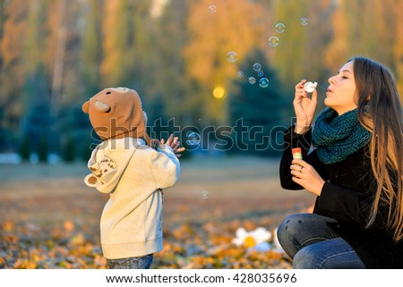 Little Boy Playing With His Sister In The Park In Autumn Girl Blowing Soap Bubbles