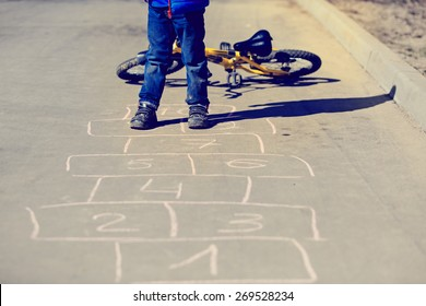 little boy playing hopscotch with bike outside