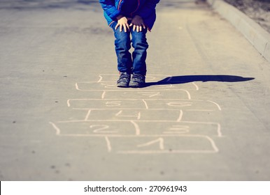 little boy playing hopscotch on driveway outside
