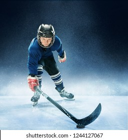 Little boy playing ice hockey at arena. A hockey player in uniform with equipment over a blue background. The athlete, child, sport, action concept