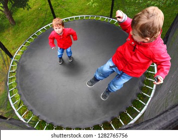Little boy playing and jumping on a outdoor trampoline. Child enjoying life during summer vacations.