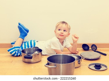 little boy playing with kitchen utensils at home