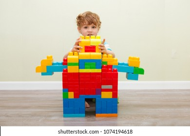Little boy playing with lots of colorful plastic blocks constructor and builds the robot indoor.